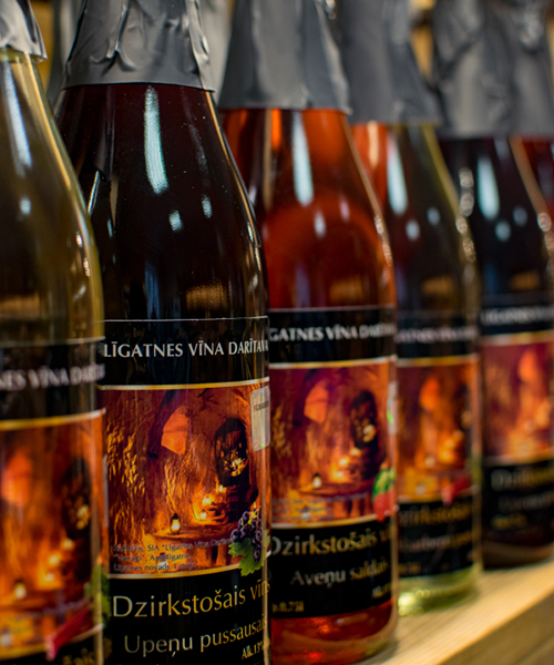 Upeņu dzirkstošais vīns plauktā